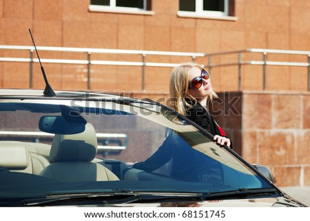 Happy young woman with a convertible car. - stock photo