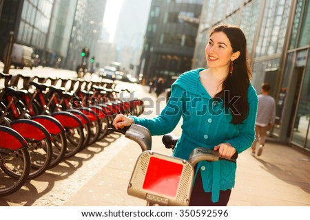 happy young woman with a hire bike in london