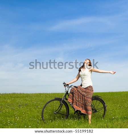 Happy young woman with a vintage bicycle on a green meadow