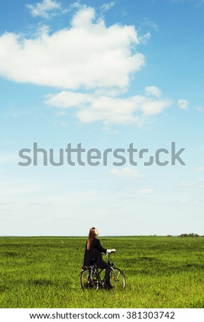 Happy young woman with a vintage bicycle on a green meadow. Young woman really anoyed beacuse of her to broken bicycle. beautiful girl on a vintage bike - stock photo
