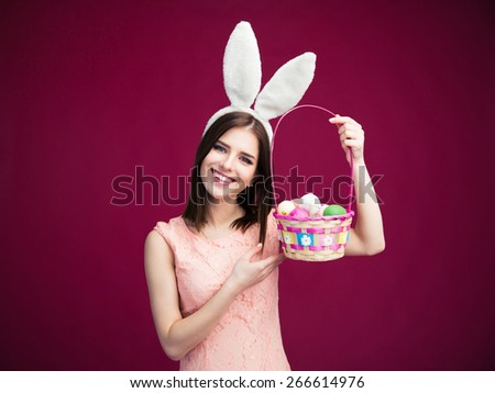 Happy young woman with an Easter egg basket over pink background. Looking at camera - stock photo