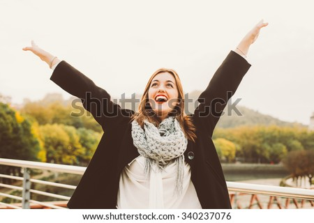 Happy young woman with arms raised celebrating something in the city - stock photo