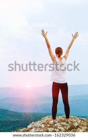 Happy young woman with arms raised. Girl standing on a cliff side - stock photo