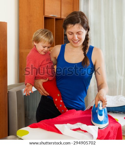 Happy young woman with baby on the ironing board ironing clothes - stock photo