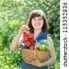 Happy young woman with basket of harvested vegetables in garden - stock photo