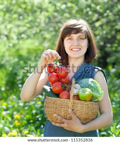 Happy young woman with basket of harvested vegetables in garden