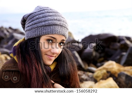 Happy young woman with big green eyes smiling on the beach - stock photo