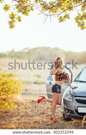 happy young woman with car - sexy rich lady driver with long blond healthy hair at automobile .summer portrait . beautiful slim fashion girl posing near car - stock photo