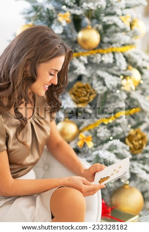 Happy young woman with christmas postcard sitting near christmas tree - stock photo