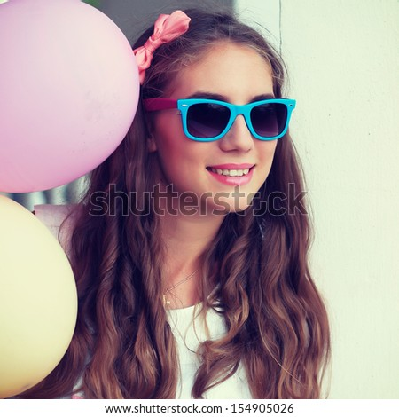 Happy young woman with colorful balloons, outdoor - stock photo