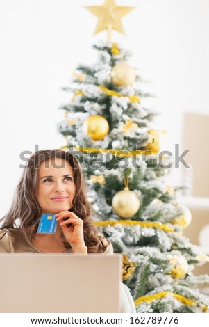 Happy young woman with credit card and laptop near christmas tree looking on copy space - stock photo