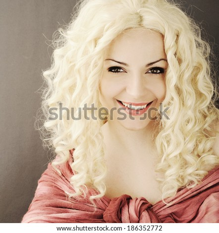 Happy young woman with curly blond hair looking at camera - stock photo