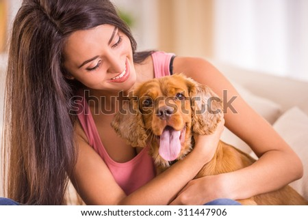 Happy young woman with dog are sitting on sofa. - stock photo