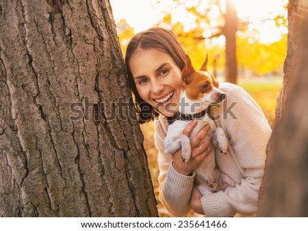 Happy young woman with dog outdoors in autumn park looking out from from tree - stock photo