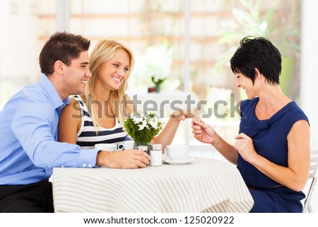 happy young woman with fiance showing her engagement ring to her mother
