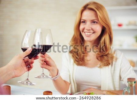 Happy young woman with glass of red wine toasting with man - stock photo