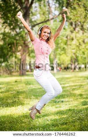 Happy young woman with headphones jumping in park and having fun. - stock photo