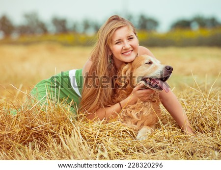 happy young woman with her dog golden retriever in rural areas in summer - stock photo
