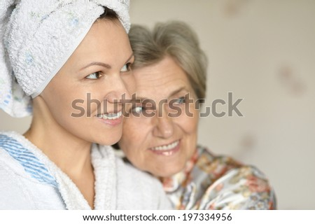 happy young woman with her elder mother at home - stock photo