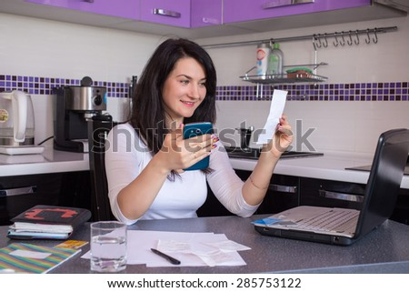 Happy young woman with laptop using credit card and phone in kitchen at home - stock photo