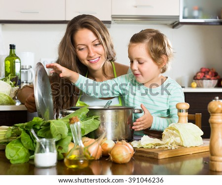 Happy young woman with little daughter cooking with vegetables at home kitchen