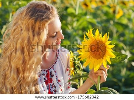 Happy young woman with long hair in the sunflower field. Summer fun - stock photo