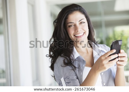 Happy young woman with mobile phone - stock photo