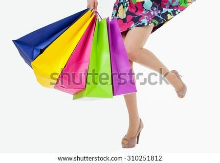 Happy young woman with multicolored shopping bags, closeup shot of female legs on white background - stock photo