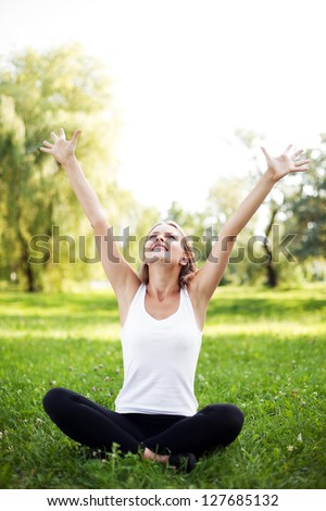 Happy young woman with raised arms sitting on grass - stock photo