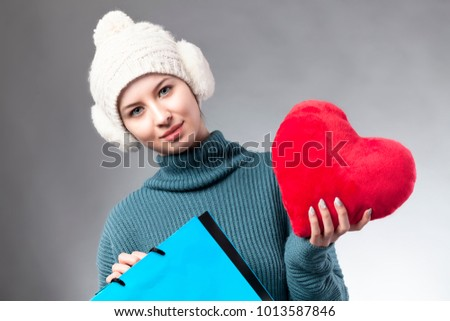 Happy young woman with shopping bags.  Winter sales icon. Valentine's shopping.