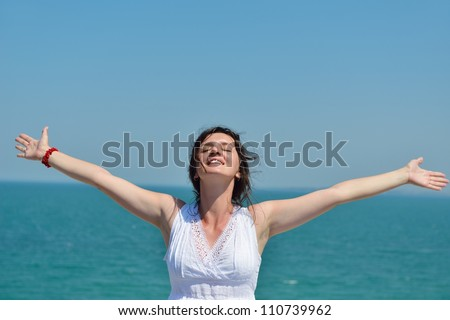 Happy  young woman with spreading arms, blue sky with clouds in background  - copy space