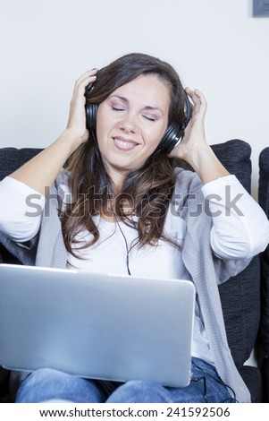 happy young woman with the eyes closed enjoy listening music sitting on a sofa at home with headphones and laptop