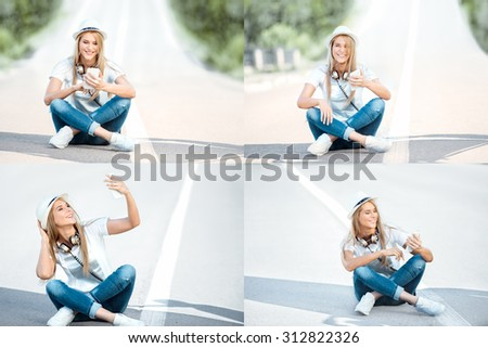 Happy young woman with vintage music headphones around her neck, surfing internet on a smartphone and sitting on a separating strip against road background.