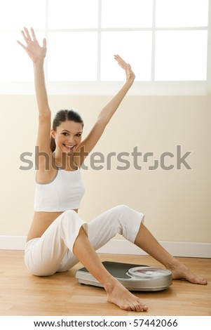 Happy young woman with weight scale - stock photo
