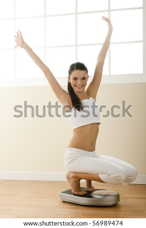 Happy young woman with weight scale weight scale - stock photo