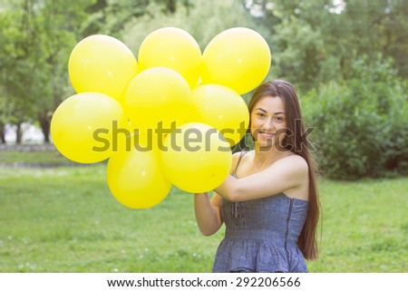 Happy Young Woman with Yellow Balloons at beautiful Summer Day Outdoor. Attractive female enjoying nature. - stock photo