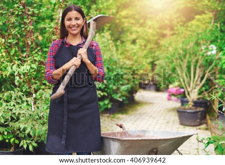 Happy young woman working at a commercial nursery holding a spade over her shoulder as she stands amongst the plants with a wheelbarrow - stock photo
