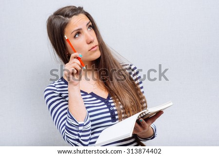 happy young woman writes something to the workbook