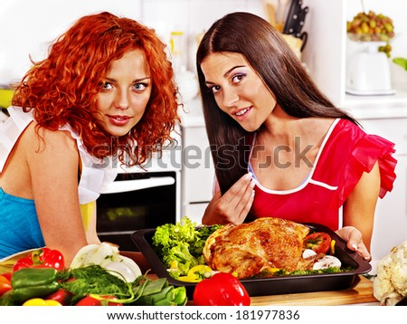 Happy young women cooking chicken at kitchen.