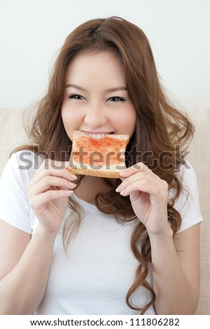 Happy Young Women Eating Bread and jam - stock photo