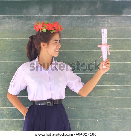 Happy young women graduate with certificate in class - stock photo