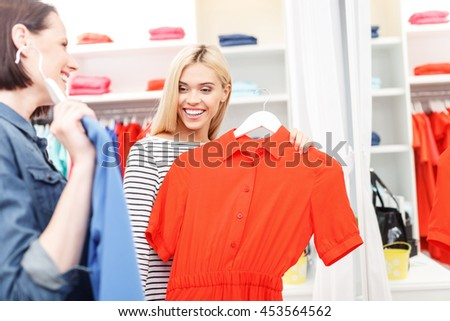 Happy young women holding up dresses in shop