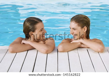 Happy young women looking at each other while leaning at poolside