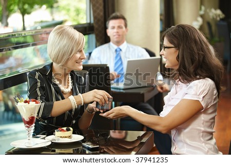 Happy young women sitting in cafe having sweets, giving birthday preasent, smiling.