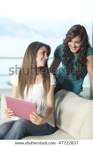 Happy young women sitting on a sofa with a pink netbook smiling to each other, mediterranean sea and mountains in the background.