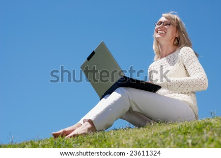 Happy young women smiling and working on a laptop outdoors - stock photo
