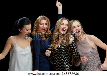 happy young women with microphone singing karaoke - stock photo