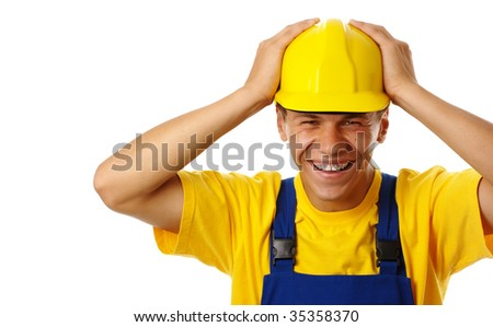 Happy young worker put his hands on hard hat, dressed in blue-and-yellow uniform, isolated over white - stock photo