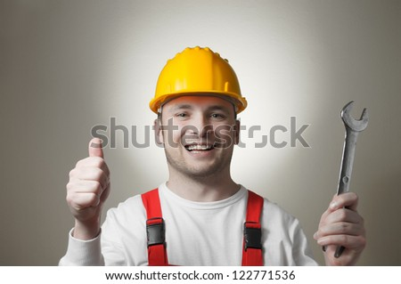 Happy young worker with a wrench - stock photo