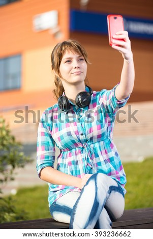 Happy young wpman taking pictures of herself through cell phone. Selfie. - stock photo